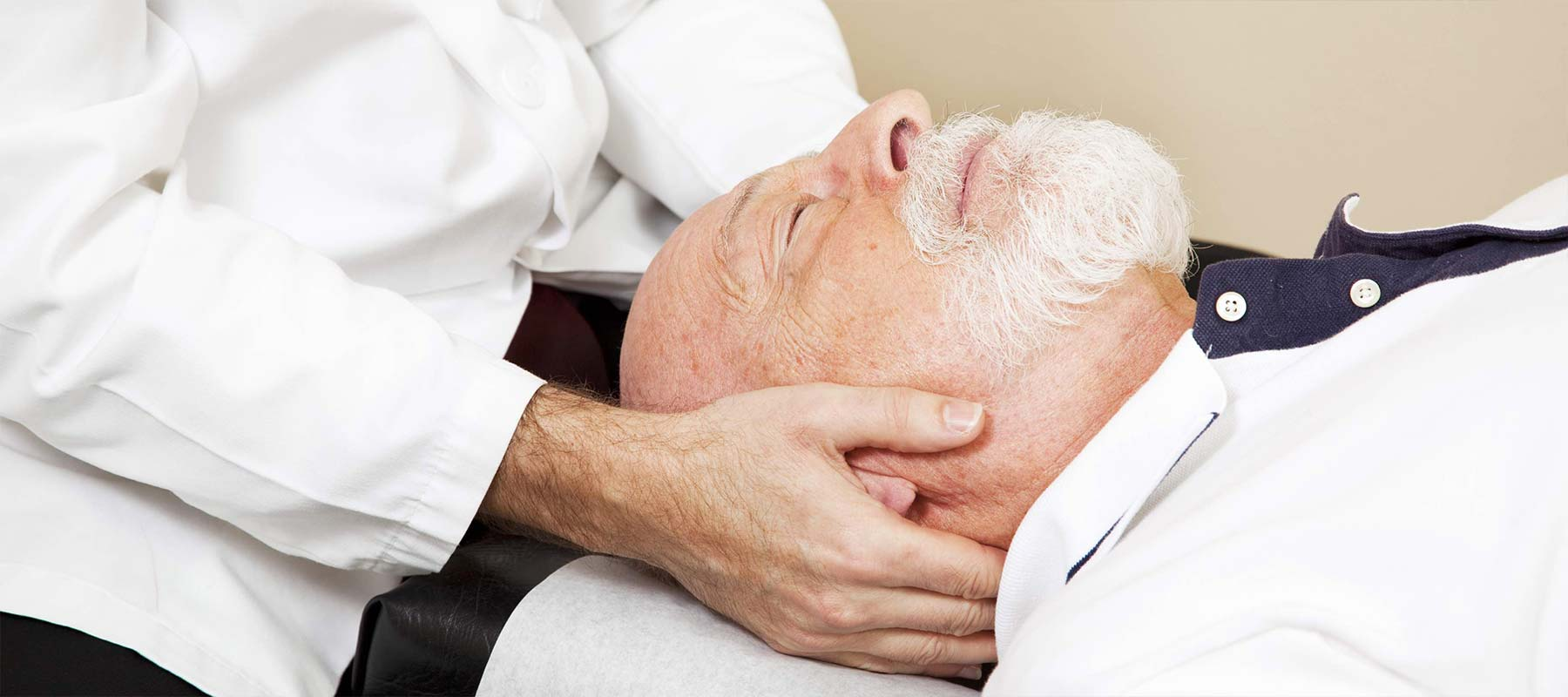 An old man receiving neck treatment